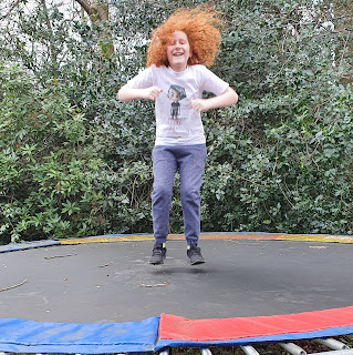 Boy on trampoline with crazy long red hair