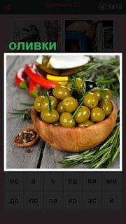 на столе стоит чаша с оливками и вокруг лежит зелень