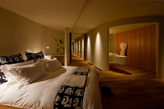 Photo of master bedroom and hallway in the background inside of circular home