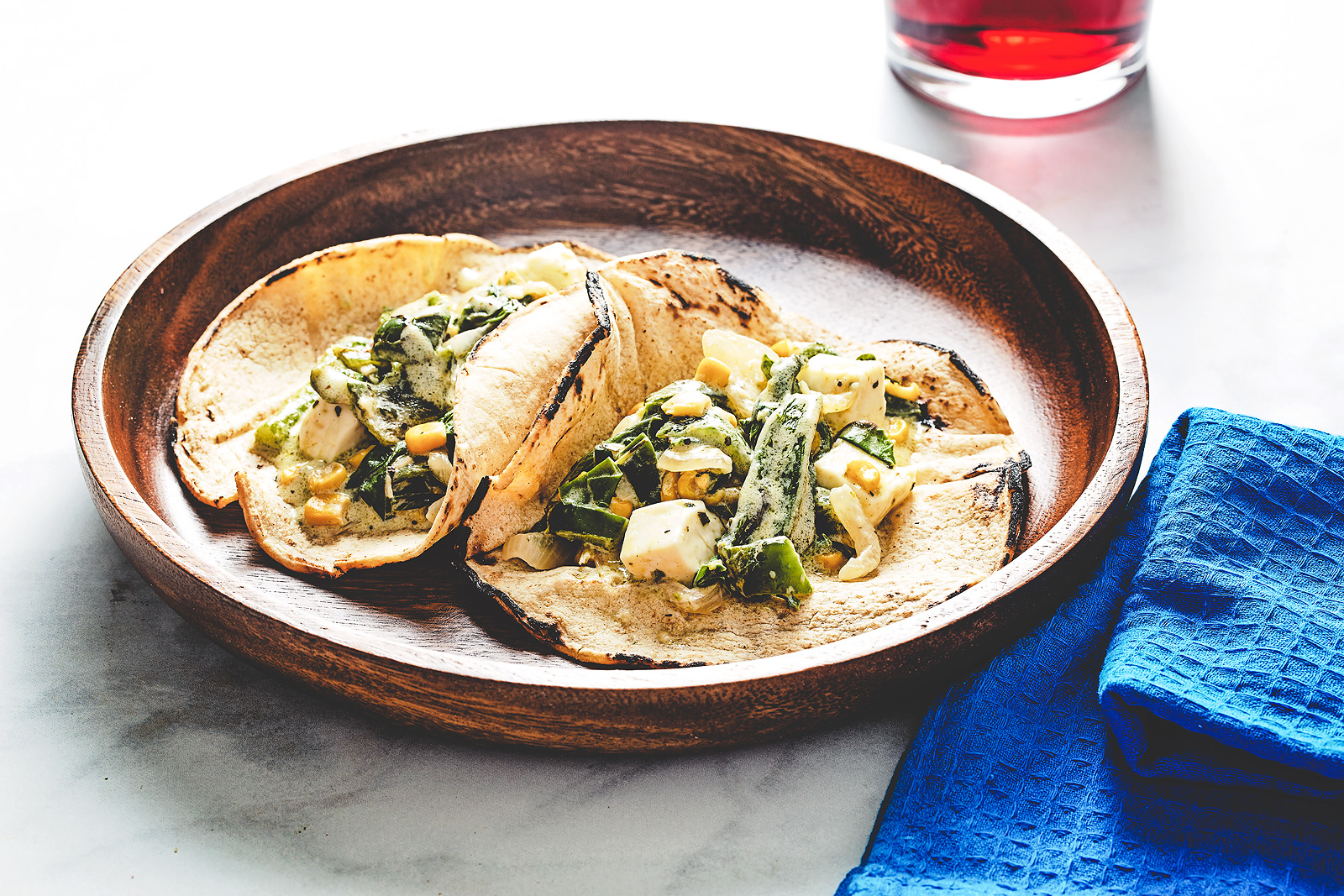 Tacos filled with roasted poblano, corn and chard in cream sauce.