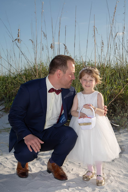 Candid photos of groom and flower girl on Fort Myers beach.