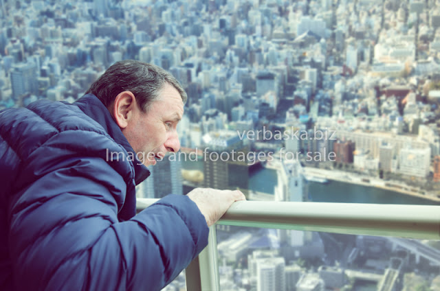 A man experiences acrophobia symptoms being on the viewing platform above a big city. He looks down with fear.