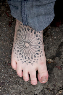 vemos a una mujer con los pies desnudos , lleva un tatuaje en el pie