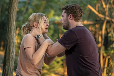 A24's 2019 Midsommar movie review and movie still where Jack Reynor comforts a crying Florence Pugh in a forest