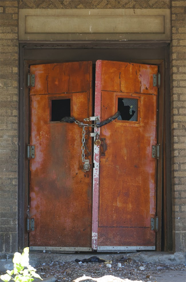 Chained rusted doors to abandoned nurses quarters building