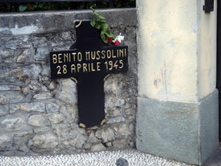 A simple cross marks the place where Mussolini and his  mistress, Claretta Petacci, were killed in a lakeside village