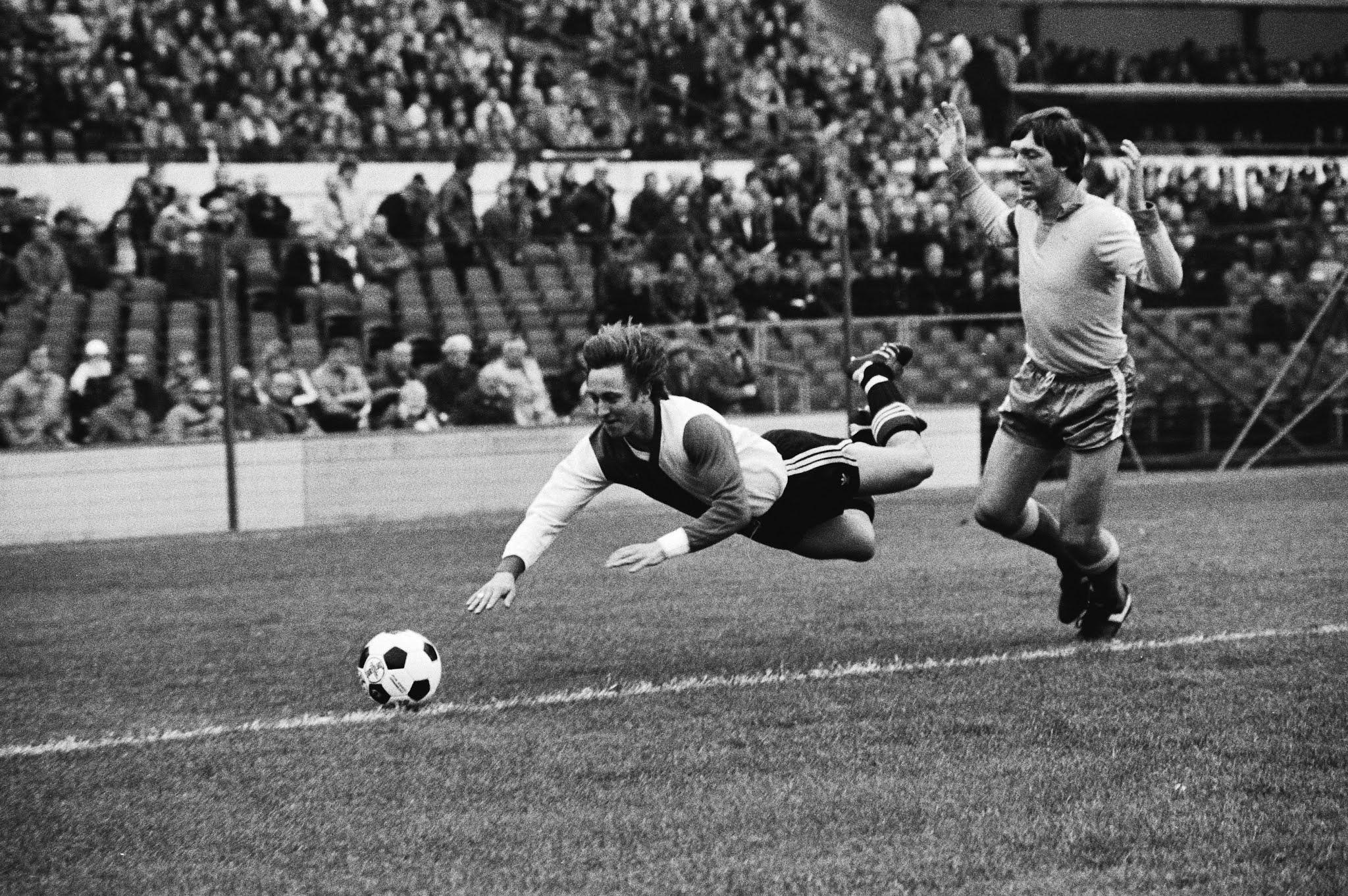 Roger Albertsen (Feyenoord) versiert een vrije trap tegen Joop Wildbret (FC Utrecht)
