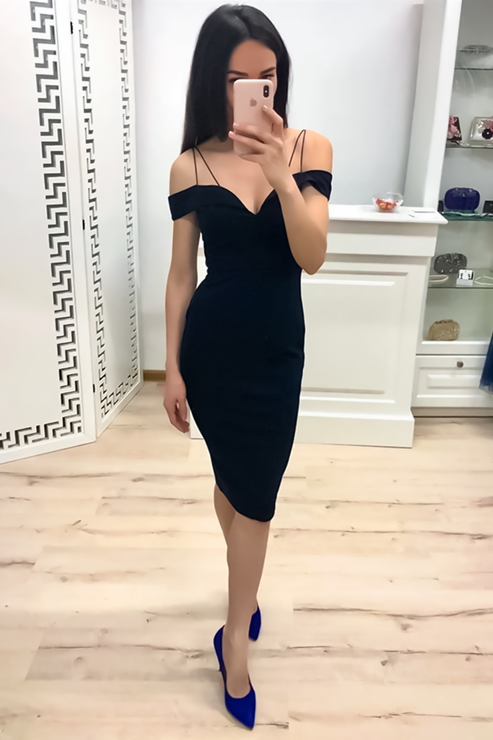 woman in a tight evening dress is posing in the room and taking a selfie