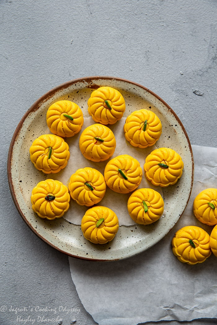 A plate full of mango peda placed on grey coloured backboard