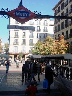 Viandantes entra y salen por la boca de Metro en el barrio de Chueca, bajo el cartel de la misma.
