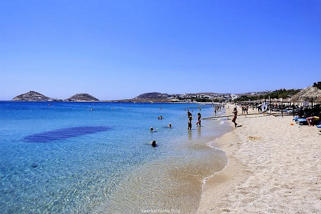 W tle dwie góry. Na pierwszym planie: plaża, turyści, greckie morze, leżaki i parasole.