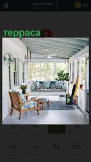 светлая терраса, на которой стоят стулья и диван с подушками