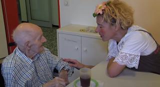 Alter Mann unterhält sich im Krankenhaus mit einem Clown.