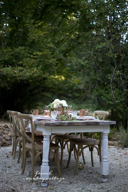 old farmhouse table on pea gravel patio set in autumn