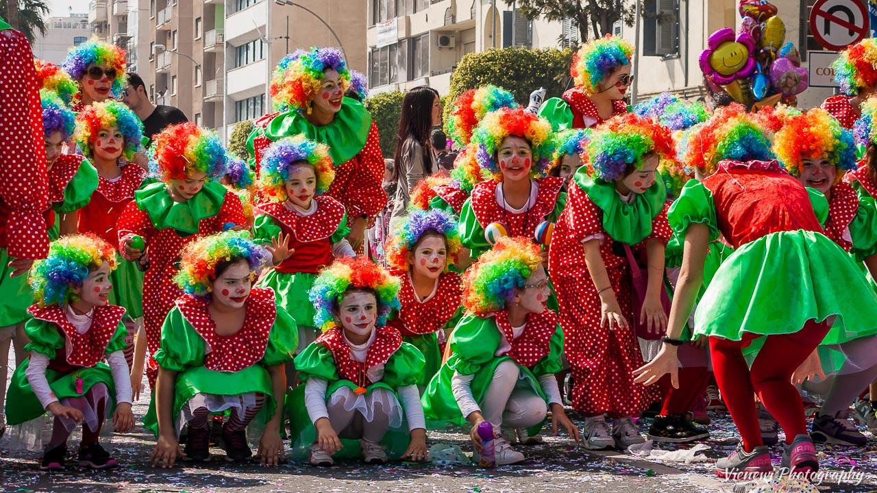 Wesoła i bardzo kolorowa grupa dzieci przebranych za klowny podczas dziecięcej parady karnawałowej w Limassol w 2014 roku.  Dzieci są naśladuja nauczycielke pokazującą. Zaczynają z przykucu.