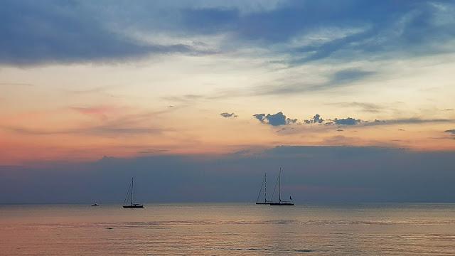 tramonto con imbarcazioni all'orizzonte