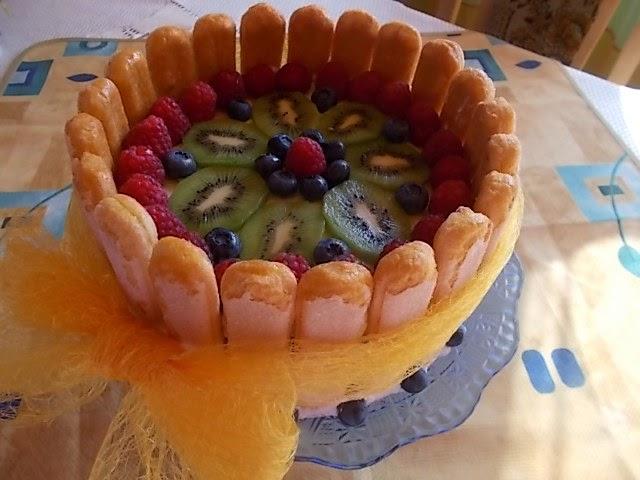 Tort z bitą śmietaną i owocami na biszkoptach.