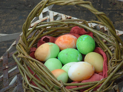 Photo of green and orange eggs in a little rustic willow basket