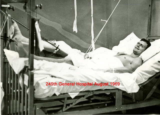 Old black and white photo of a man in a hospotal bed with his legs elevated