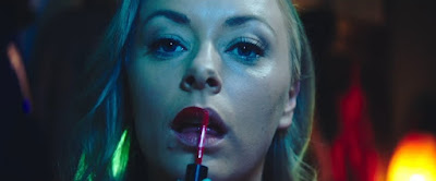 Eve (2019) movie still where Rachel Warren applies lip gloss in front of the camera
