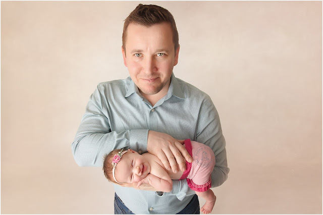 Newborn baby girl in a pink skirt and pink flower headband smiles while her daddy is holding her in his hands.