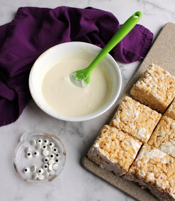 rice crispy treat rectangles next to a bowl of melted white chocolate and eye balls to make mummies