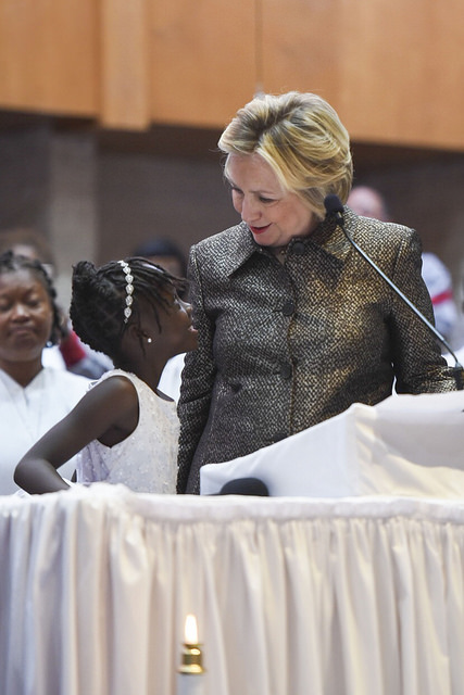 image of Hillary Clinton at a campaign event at a church, talking to a little Black girl in a white dress, who is looking up at her with a joyful expression