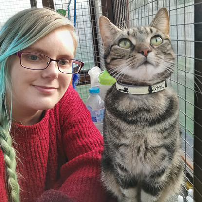 blonde woman in red jumper next to tabby cat wearing collar