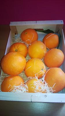 Offene Holzkiste mit großen Orangen