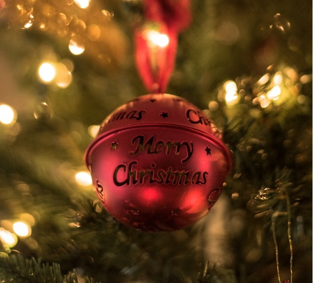 Red bell bauble with Merry Christmas on the front hanging on a tree