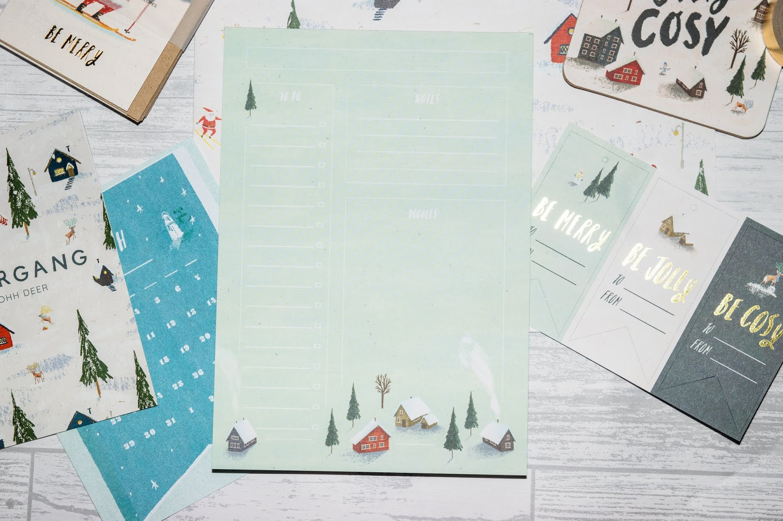 A minty blue list pad with a forest winter designed illustration on the bottom.