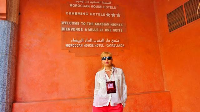 Изображение туристки на фоне таблички отеля в Касабланке