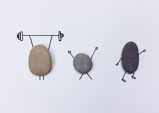 Photo of three rocks with arms and legs drawn on paper behind them to make it look like one is lifting weights, one is lifting up arms in triumph, and one is running