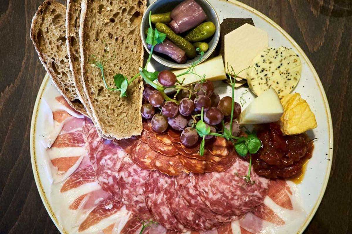 charcuterie board with baked sourdough bread and olives.