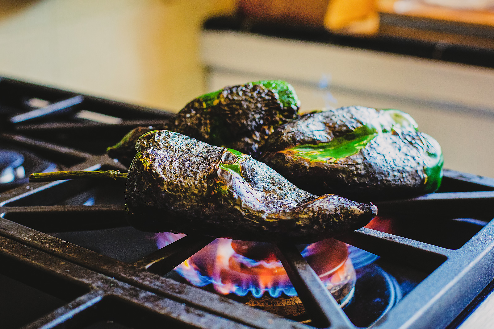 Three poblano peppers roasted directly on the grate of a gas stove.