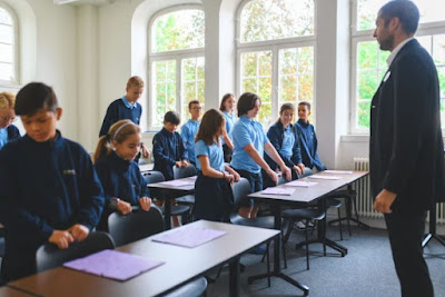Lärare står vid katedern och barnen vid sina skolbänkar i skoluniform.