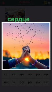 две руки вместе над которыми из капель образовалось сердце на фоне солнца