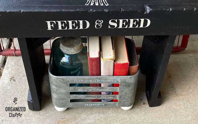 Foto de um recipiente galvanizado com livros e um frasco.