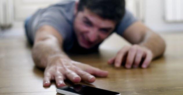 djalë i shtrirë duke u përpjekur për të kapur telefonin