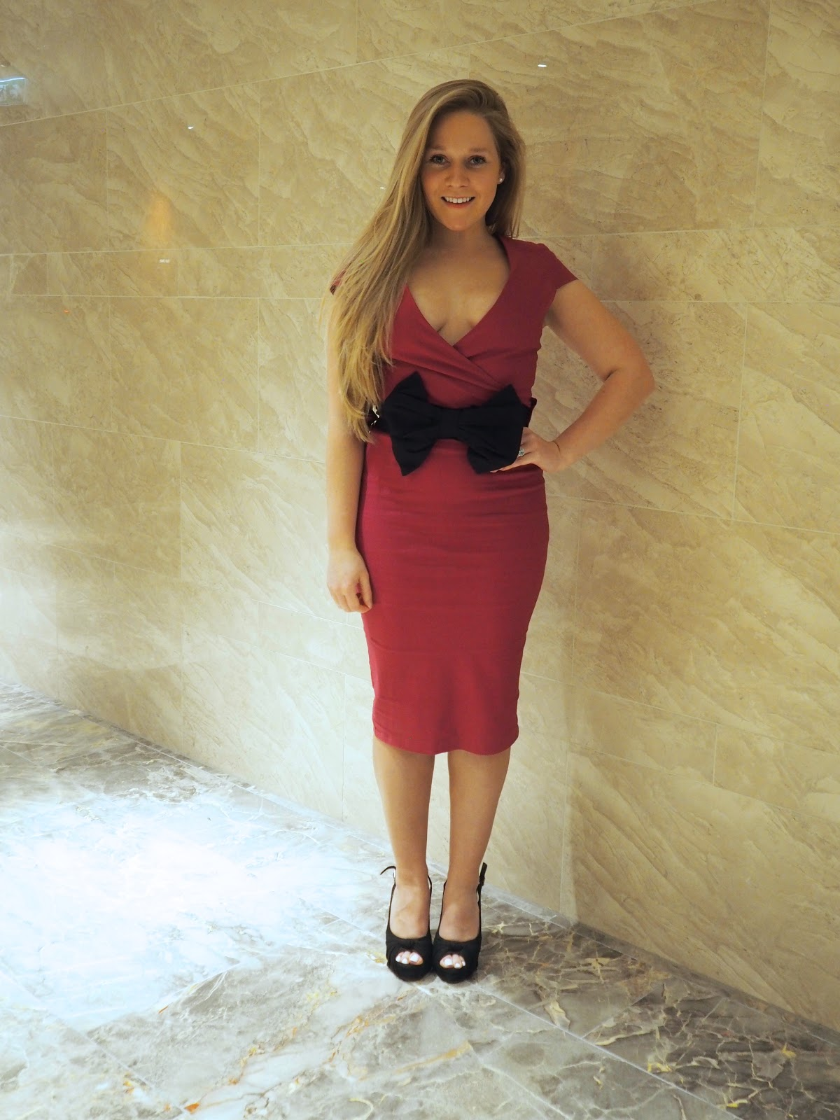 Blonde girl in pink Vesper Dress with bow standing against marble wall and floor