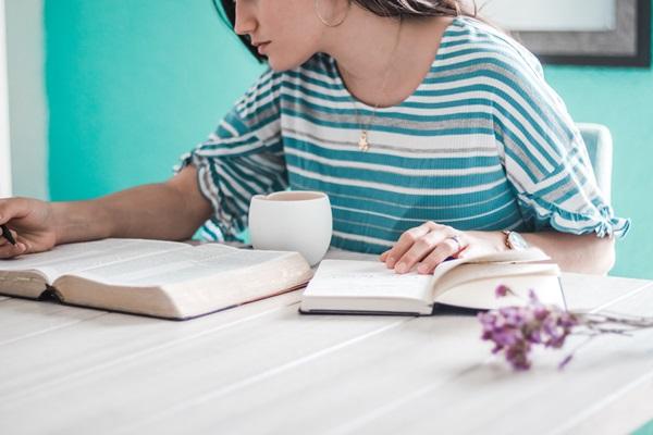 Mulher sentada vestindo azul lendo a bíblia enquanto faz anotações