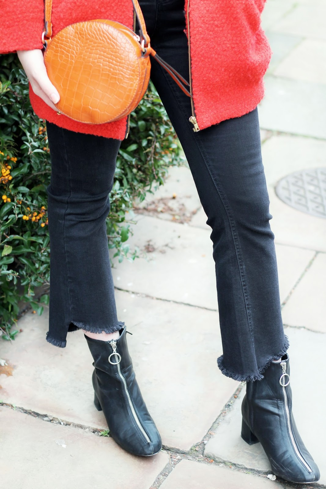 burned orange mock croc round bag, orange boucle coat, black kick flare jeans with step hem, black boots with zip detail