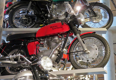 Cafe racer displayed on rack with other motorcycles.