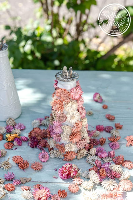 Sommerliche Kerzenständer aus Glasflaschen und Trockenblumen.