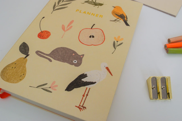An A5 linen planner with animals and plants on the front