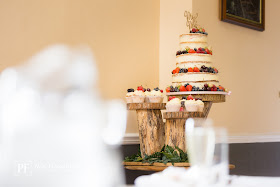 three tier wedding cake on wooden cake stand covered in fresh fruit