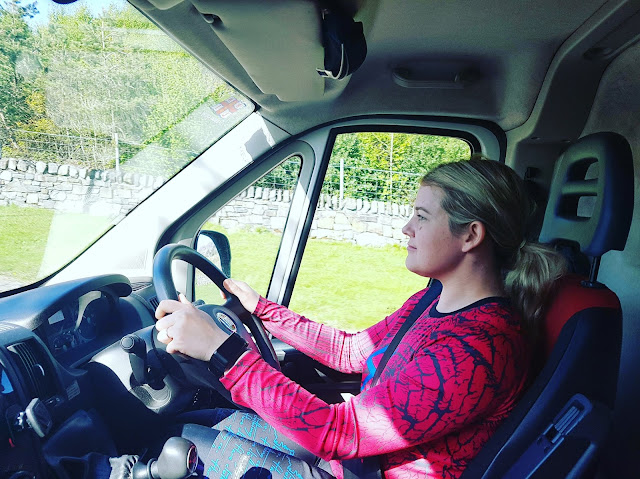 woman in pink top driving big van