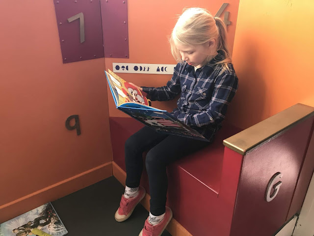 A girl sitting in a reading corner fully absorbed in a book