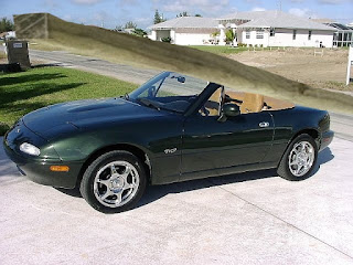 "Green 1997 Mazda Miata convertible with a pressure treated post 8""x8"" 16' on top."