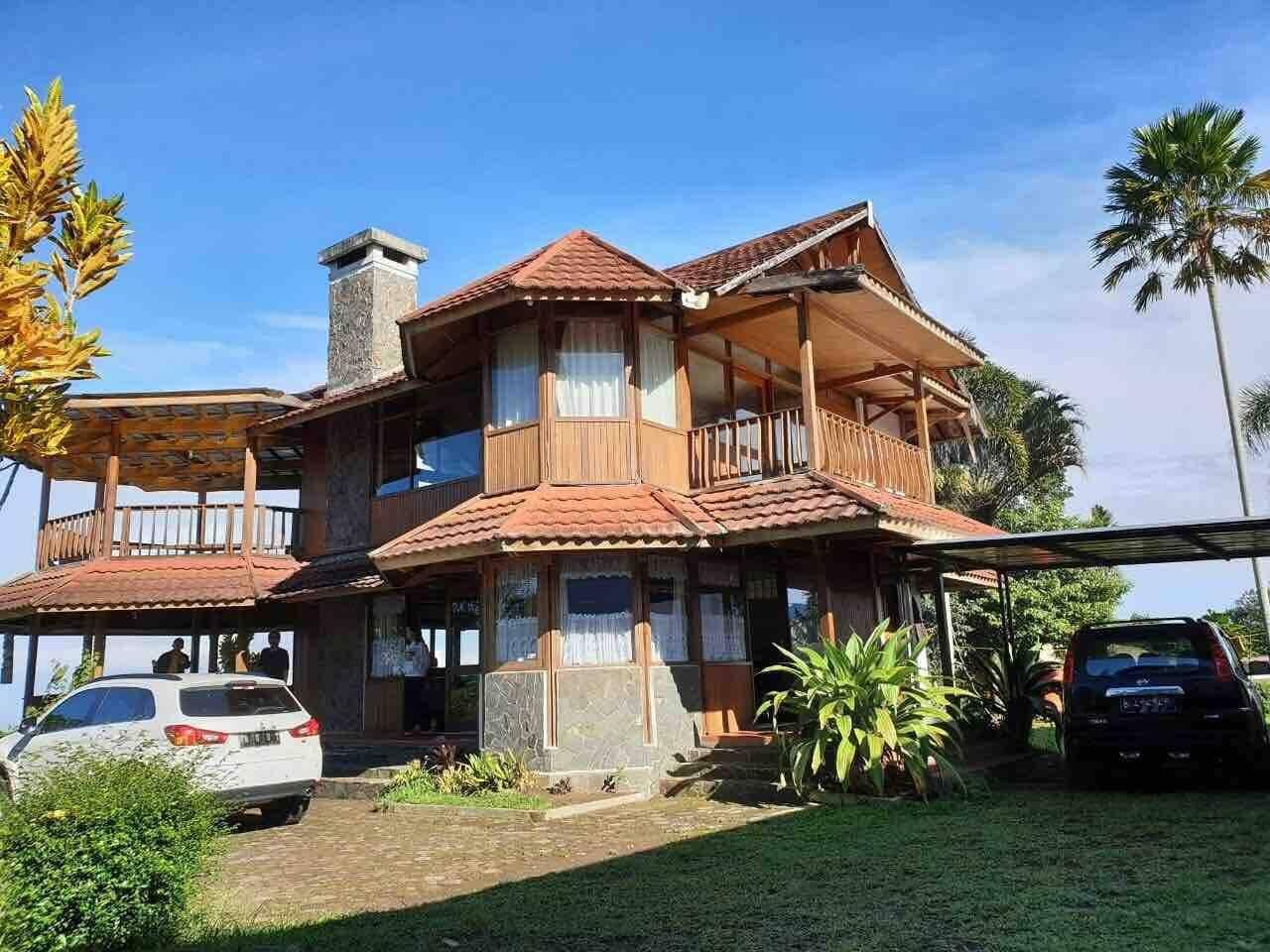 villa kayu ada perapian dan kolam renang di puncak